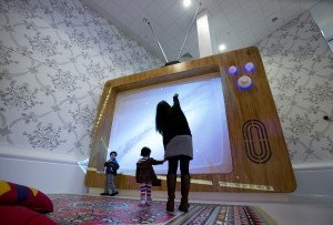 A woman and young children interact with a giant television set at the Ann Riches Healing Space for young patients at the Royal London Hospital in London February 22, 2013. REUTERS/Neil Hall (BRITAIN - Tags: HEALTH SOCIETY) - RTR3E4TN